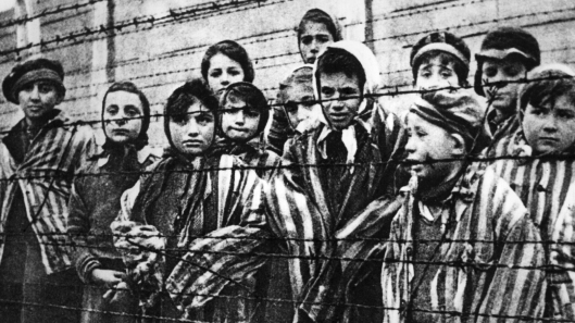 Children behind a barbed wire fence at the Nazi concentration camp at Auschwitz in southern Poland.   (Photo by Keystone/Getty Images)